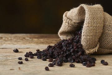 Black raisins in burlap bag over wooden table