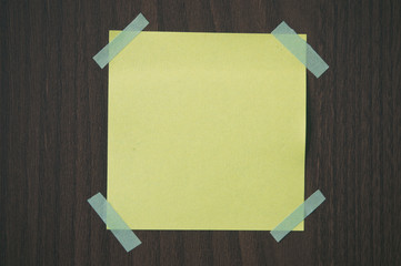 A blank sticky note with a notebook on the wall