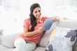Smiling brunette sitting on her sofa using tablet