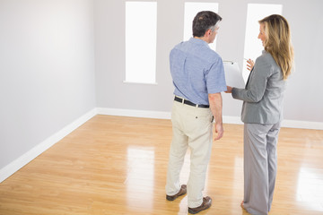 Blonde realtor showing a room and some documents to a potential