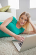 Smiling woman lying on floor using laptop