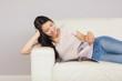Cheerful asian girl lying on the sofa reading a magazine