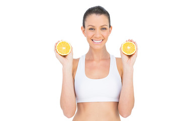 Smiling woman holding slices of orange looking at camera