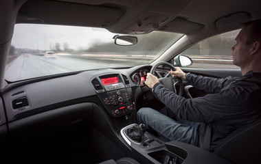 A man driving a car at speed in wet weather conditions.