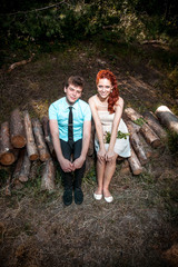 Young couple sitting on the logs