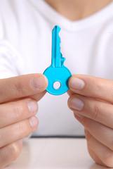 Manos de una mujer sujetando una llave azul.