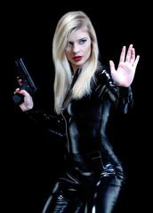 Mujer rubia sujetando una pistola.