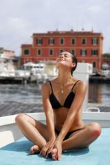 Joven mujer latina tomando sol en una barca,vacaciones.