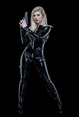 Mujer rubia con traje negro sujetando una pistola.