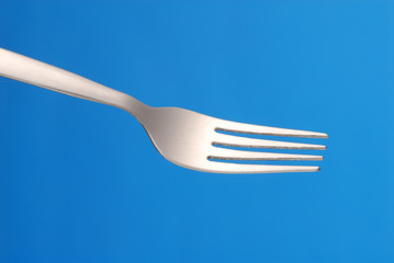 Tenedor en fondo azul.