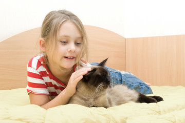 girl with a cat lying on the bed