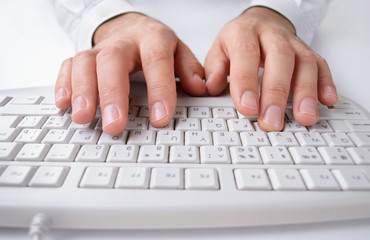 Man typing on a computer keyboard