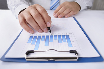 Businessman working at his desk on a graph