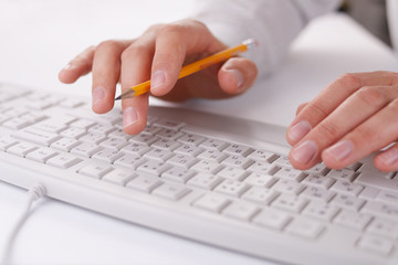 Man typing on a computer keyboard at work