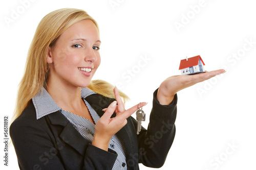 Lächelnde Geschäftsfrau mit Haus und Schlüssel
