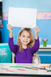 Girl Holding Blank Paper At Desk In Classroom