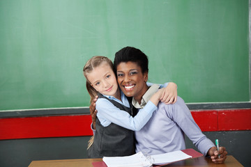 Happy Schoolgirl Hugging Teacher At Desk