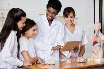 Teacher Looking At Schoolgirls While Using Tablet In Biology Cla