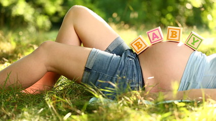 Pregnant woman lying in grass with baby blocks on her belly