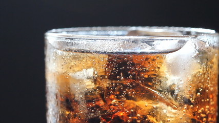 cola and ice in glass, bubble float, black background