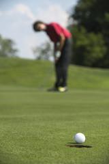 Golfer sinking a putt