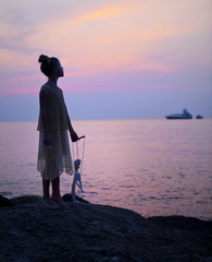 Silhouette of a girl with a puppet on a background of sea sunset