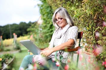 Senior woman using digital tablet in home garden