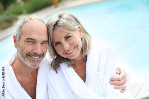 Happy senior couple in bathrobe by resort pool