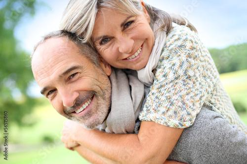 Senior man giving piggyback ride to woman