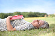 Senior woman reading book laid on the grass