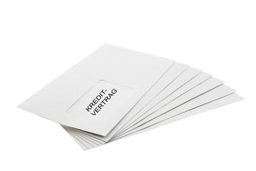 Kreditvertrag on a Batch of Envelopes isolated on White