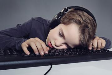 enfant garçon dormant sur son clavier d'ordinateur