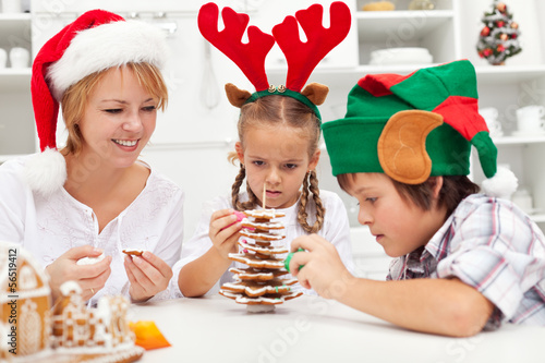Happy family making a gingerbread cookie christmas tree