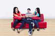 Three young friends fighting for a remote
