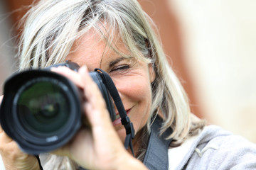 Portrait of mature woman shooting with photo camera