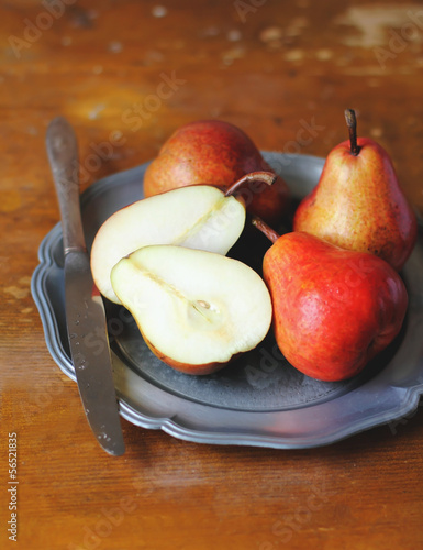 Fresh ripe pears in a plate with knife