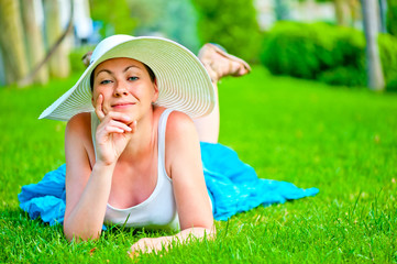 girl lies on a green lawn in a white hat