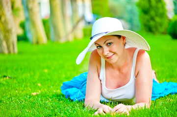 girl lies on the grass and looking at the camera