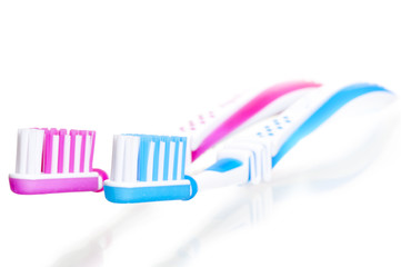 two toothbrushes are on white background