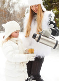 Happy young mother with daughter on winter picnic
