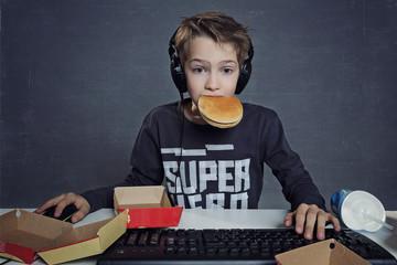 enfant jouant sur ordinateur en mangeant hamburger