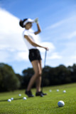 Girl playing golf on grass in summer