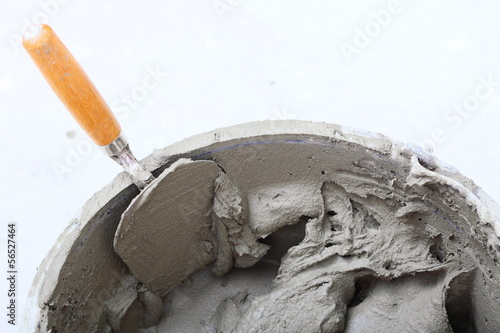 dirty trowel and bucket on building site