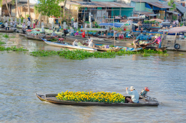 The man and colorful flowers boat at Nga Nam floating market, So