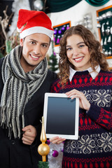 Happy Couple Showing Digital Tablet At Christmas Store