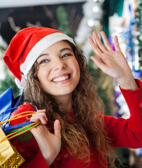 Woman Waving While Carrying Shopping Bags At Christmas Store
