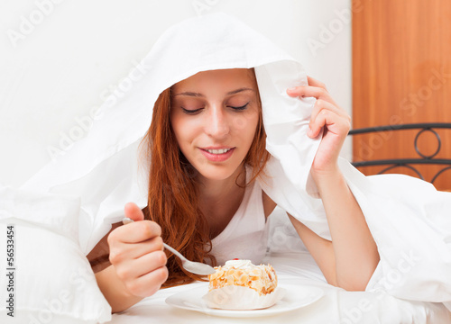 woman eating sweet cake under  in bed