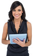 Smiling elegant brown haired model using tablet-computer
