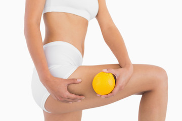 Slender female body holding orange and squeezing her thigh
