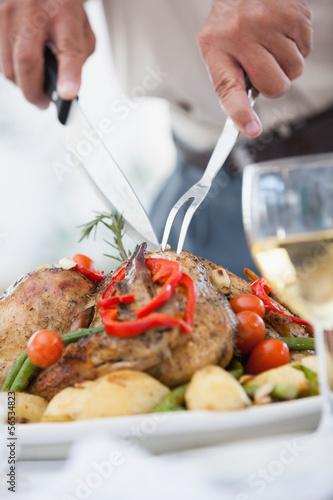 Close up of a man carving the roast chicken